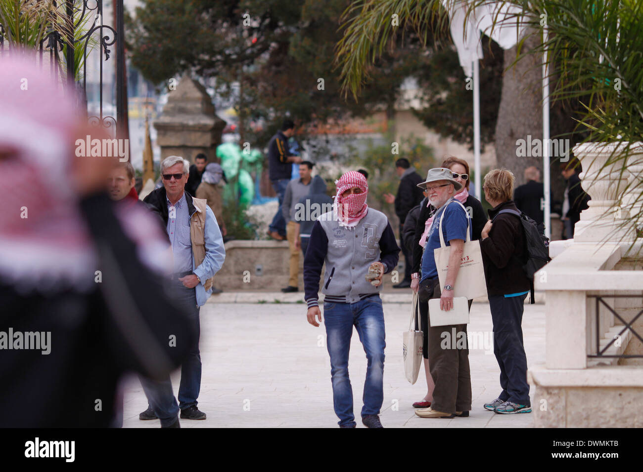 Masked Palestinians in front of Bethlehem Intercontinental Hotel among American tourists during clashes in the area. - Stock Image