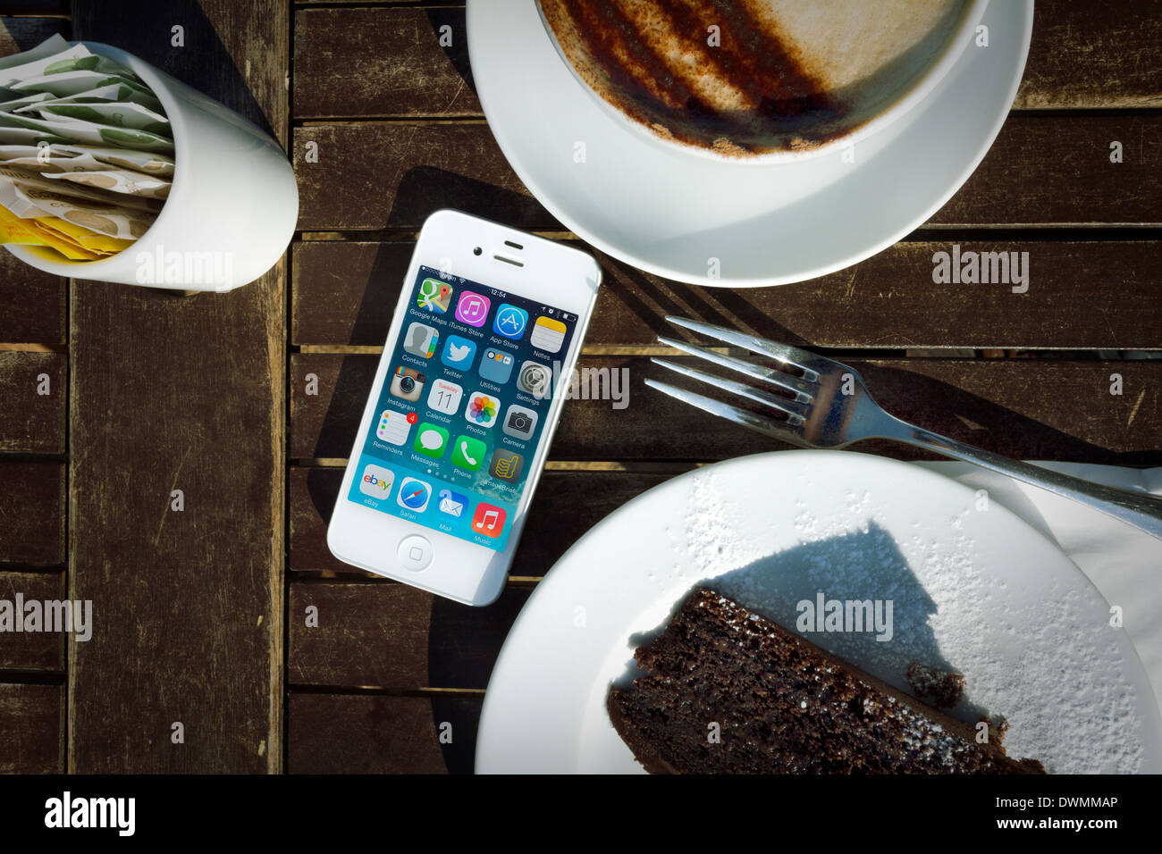 iPhone 4s On Table With Cake And Cappuccino Stock Photo