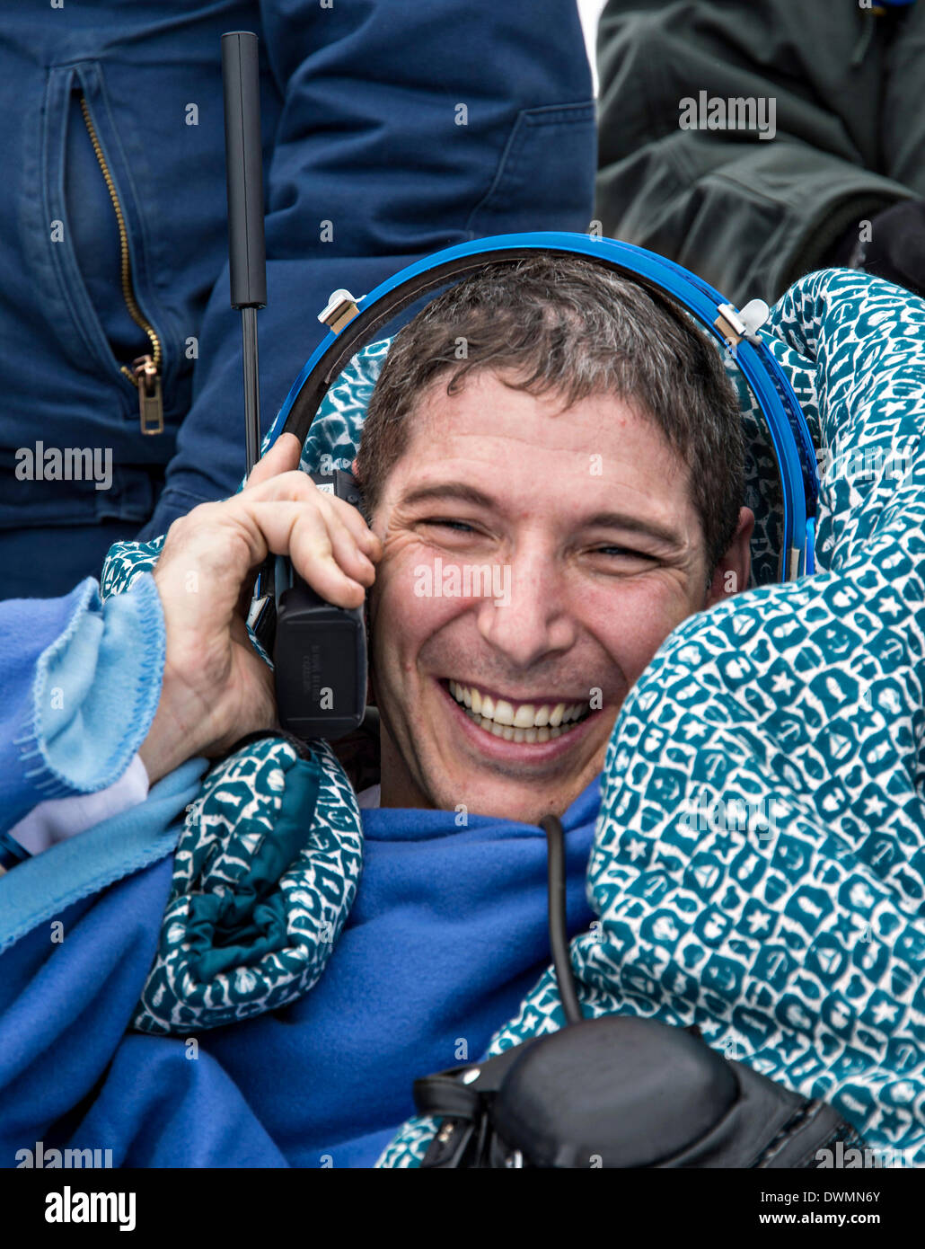 International Space State Expedition 38 astronaut Mike Hopkins of NASA talks to his family via satellite phone outside the Soyuz Capsule after landing in a Soyuz TMA-10M spacecraft March 11, 2014 near the town of Zhezkazgan, Kazakhstan. Hopkins, Kotov and Ryazanskiy returned to Earth after five and a half months onboard the International Space Station where they served as members of the Expedition 37 and 38 crews. - Stock Image