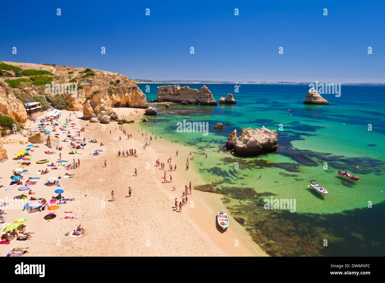 Holidaymakers sunbathing on Praia da Dona Ana, sandy beach near the resort of Lagos, Algarve, Portugal, Europe - Stock Image