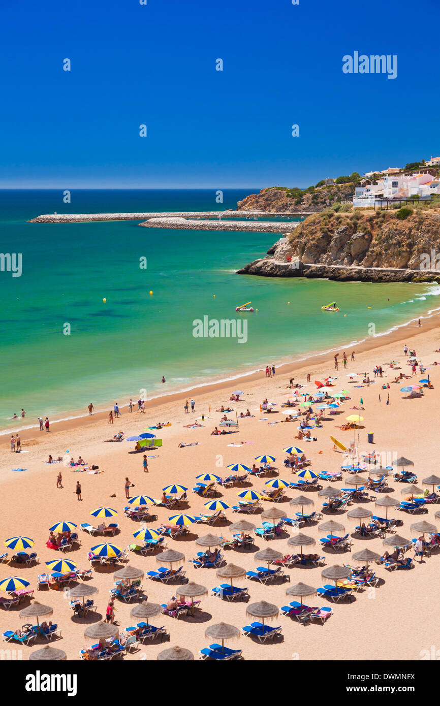Holidaymakers sunbathing under beach umbrellas on the sandy beach at Praia do Tunel, Albufeira Beach, Algarve, Portugal, Stock Photo