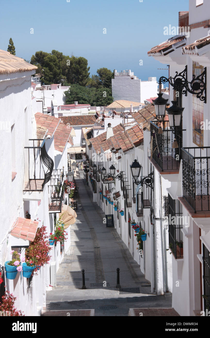 Sunny day in Spain, walking and surrounded by white walls going down the path in a small village in Mijas. Traveling destination - Stock Image