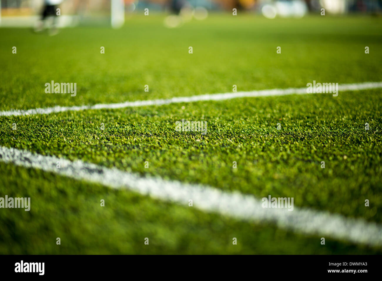 Close-up of artificial turf. Blurred legs of soccer players in the background. - Stock Image