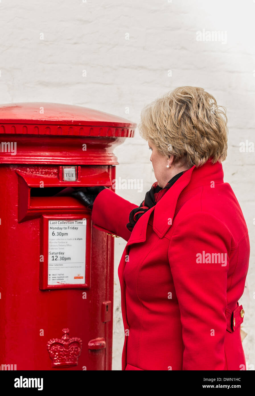 Female in a red coat posting a letter - Stock Image