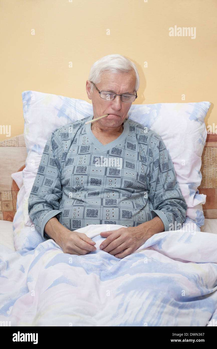 Ill senior man checking temperature with thermometer in bed. - Stock Image