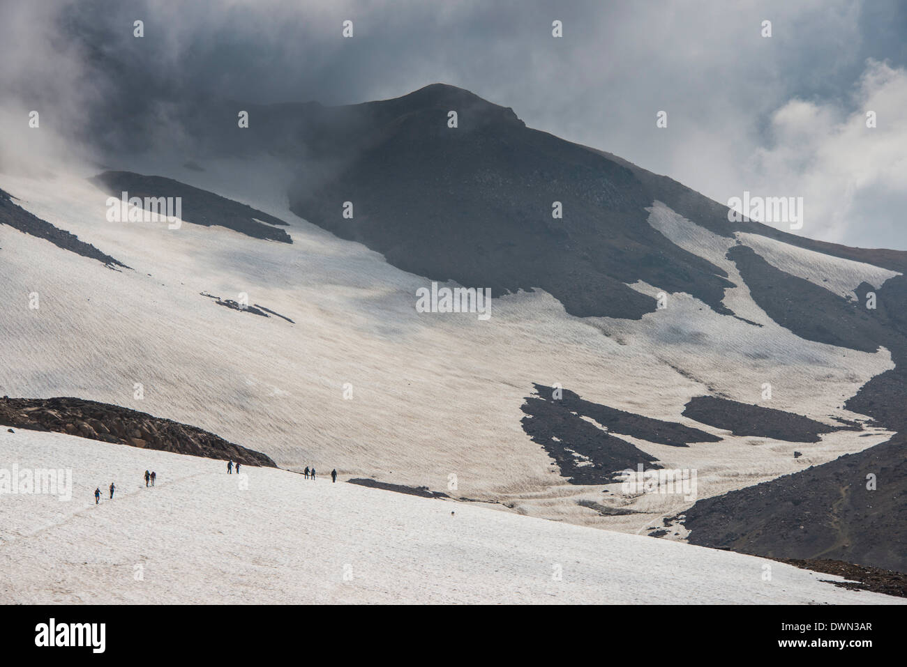 Tourists crossing a snowfield, Mutnovsky volcano, Kamchatka, Russia, Eurasia - Stock Image