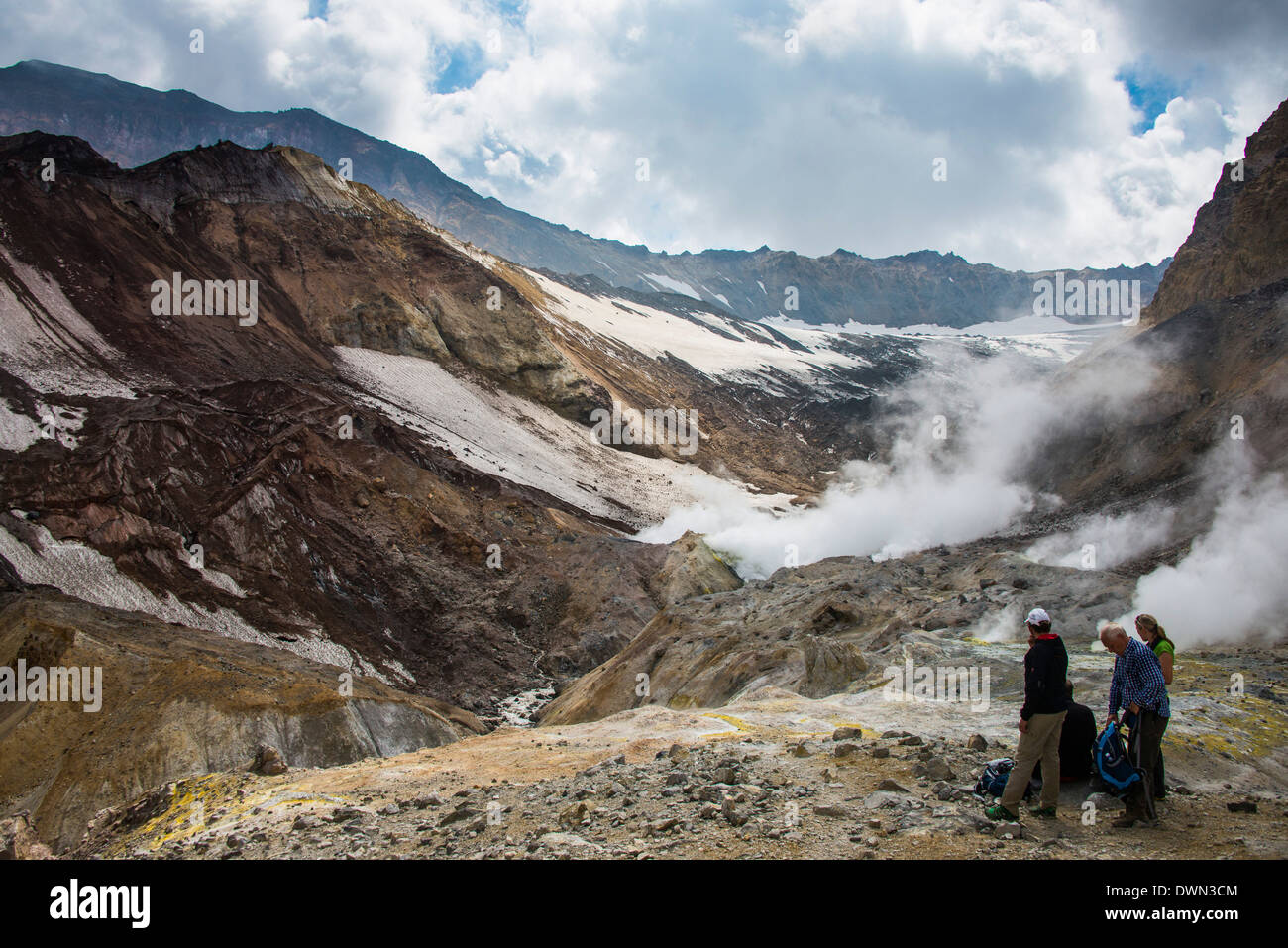 Tourists standing by smoking fumaroles on Mutnovsky volcano, Kamchatka, Russia, Eurasia Stock Photo