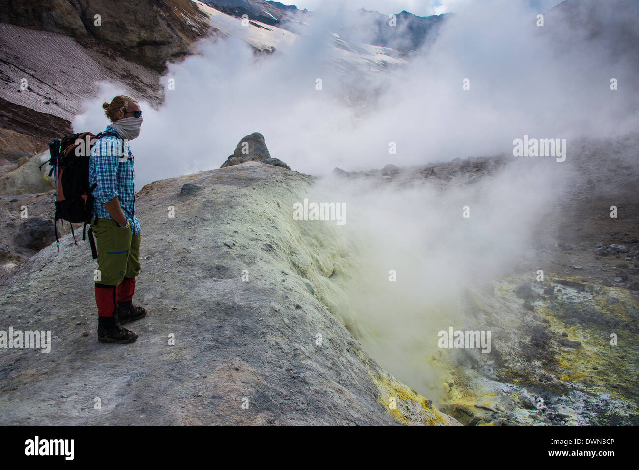 Tourists standing by smoking fumaroles on Mutnovsky volcano, Kamchatka, Russia, Eurasia - Stock Image