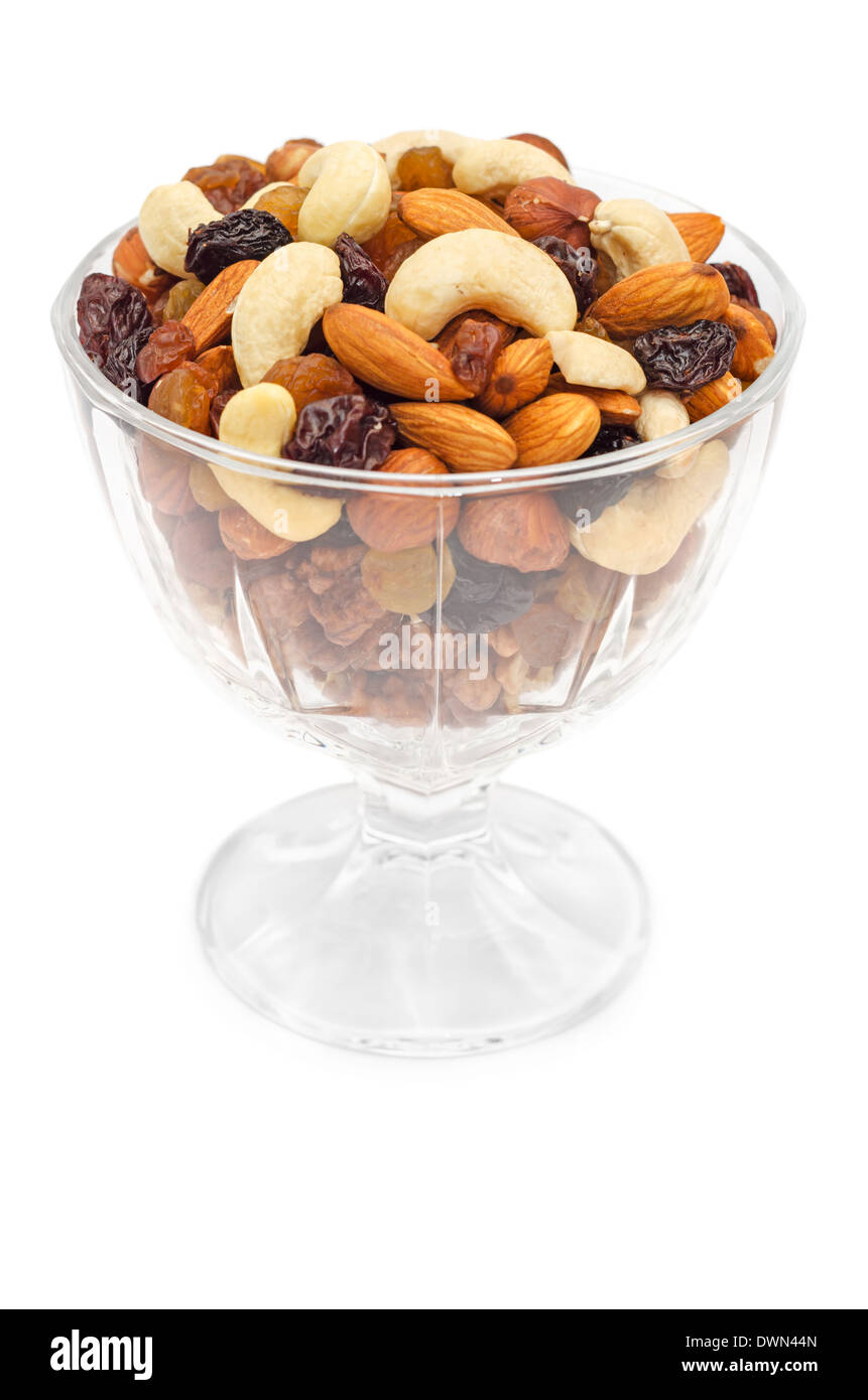 Mixed nuts and dry fruits in glass bowl isolated over white background - Stock Image