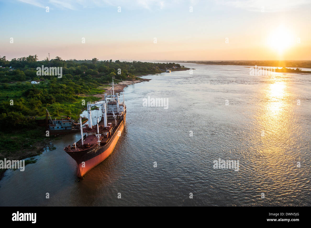 Cargo boat at sunset on the Asuncion River, Paraguay, South America - Stock Image