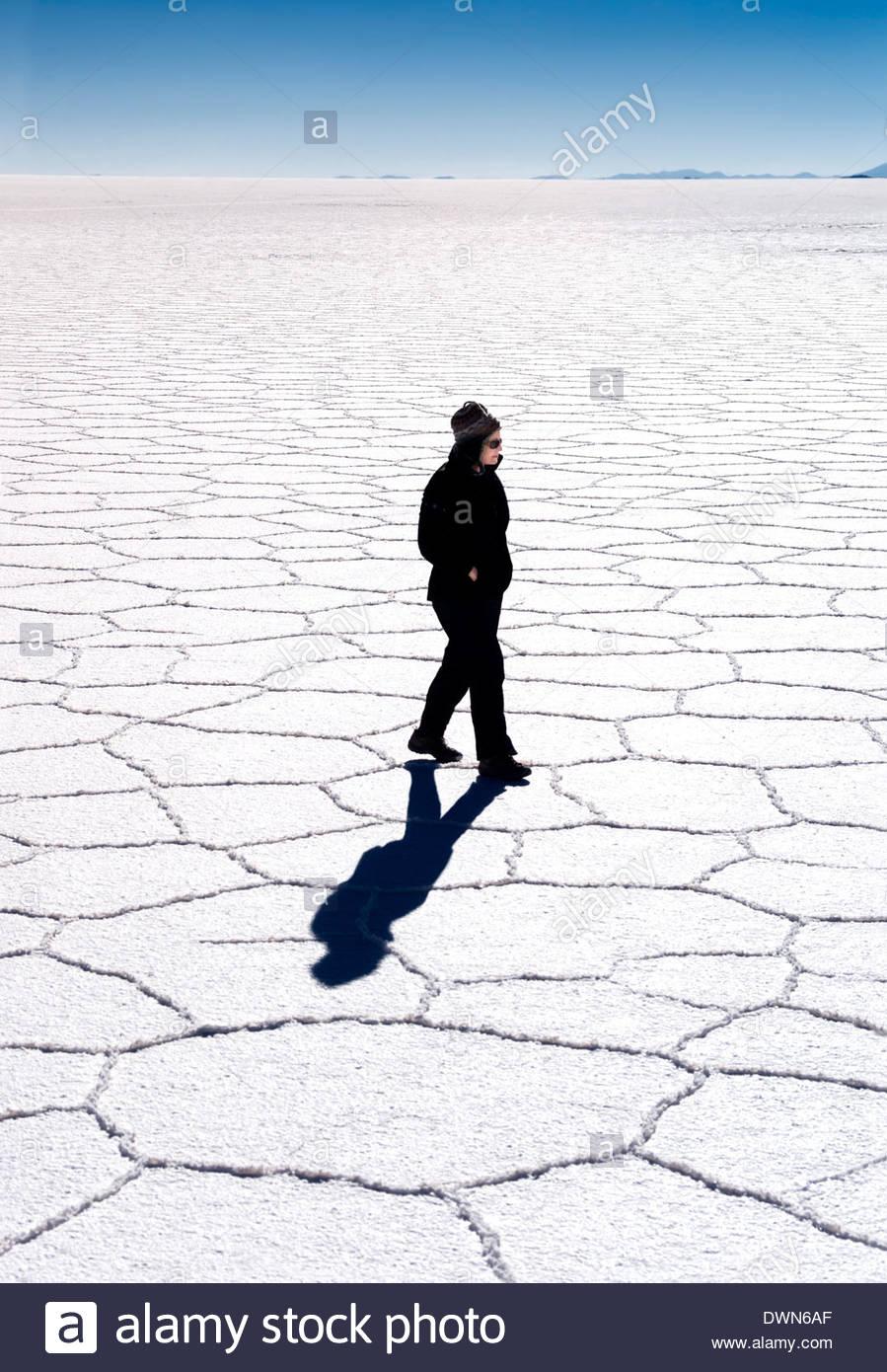 Woman walking across hexagonal patterns on salt flats, Salar de Uyuni, Bolivia, South America - Stock Image