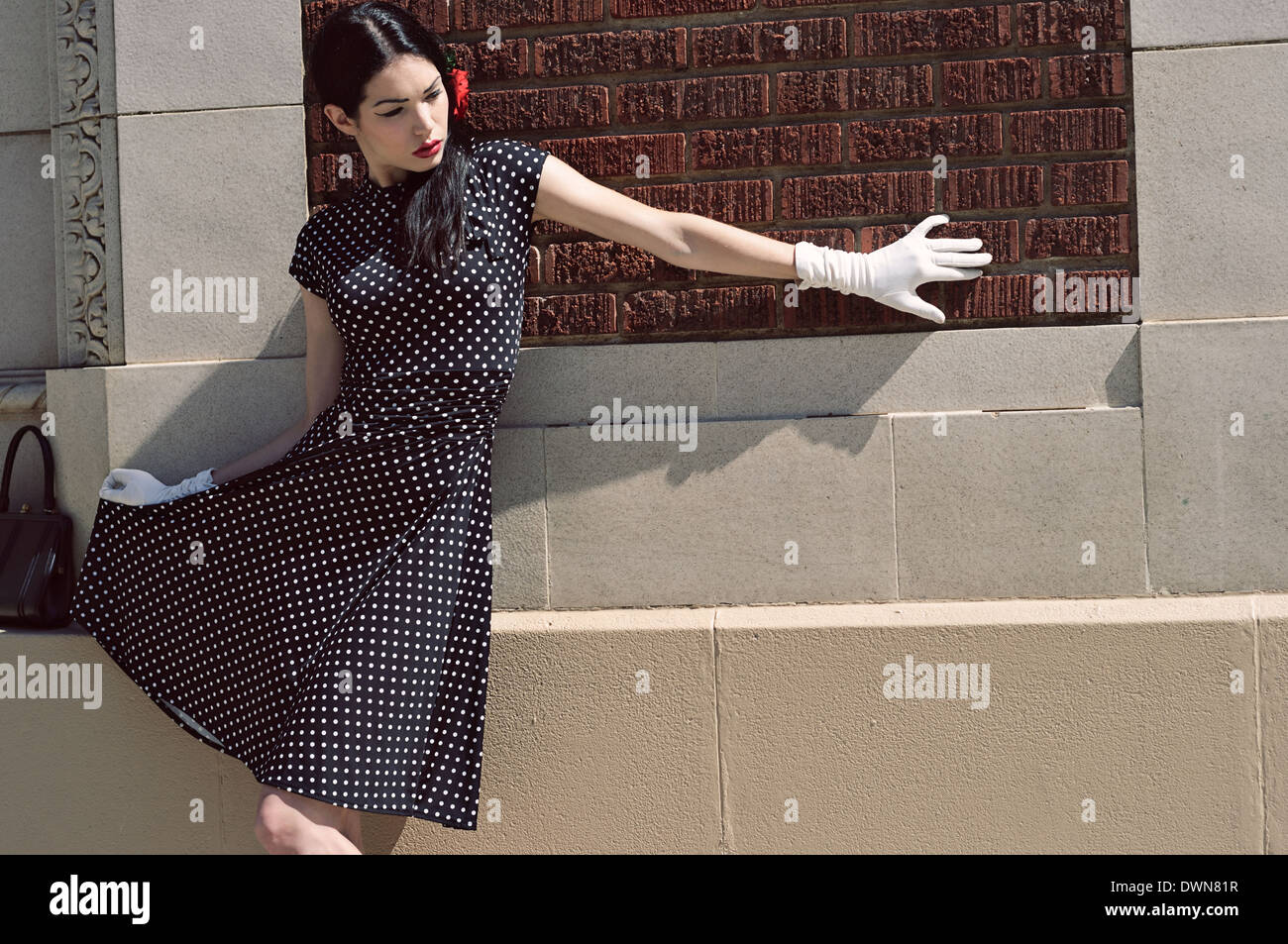 A female model lean against a wall wearing a vintage inspired polka dot dress and white glove holding up her skirt Stock Photo