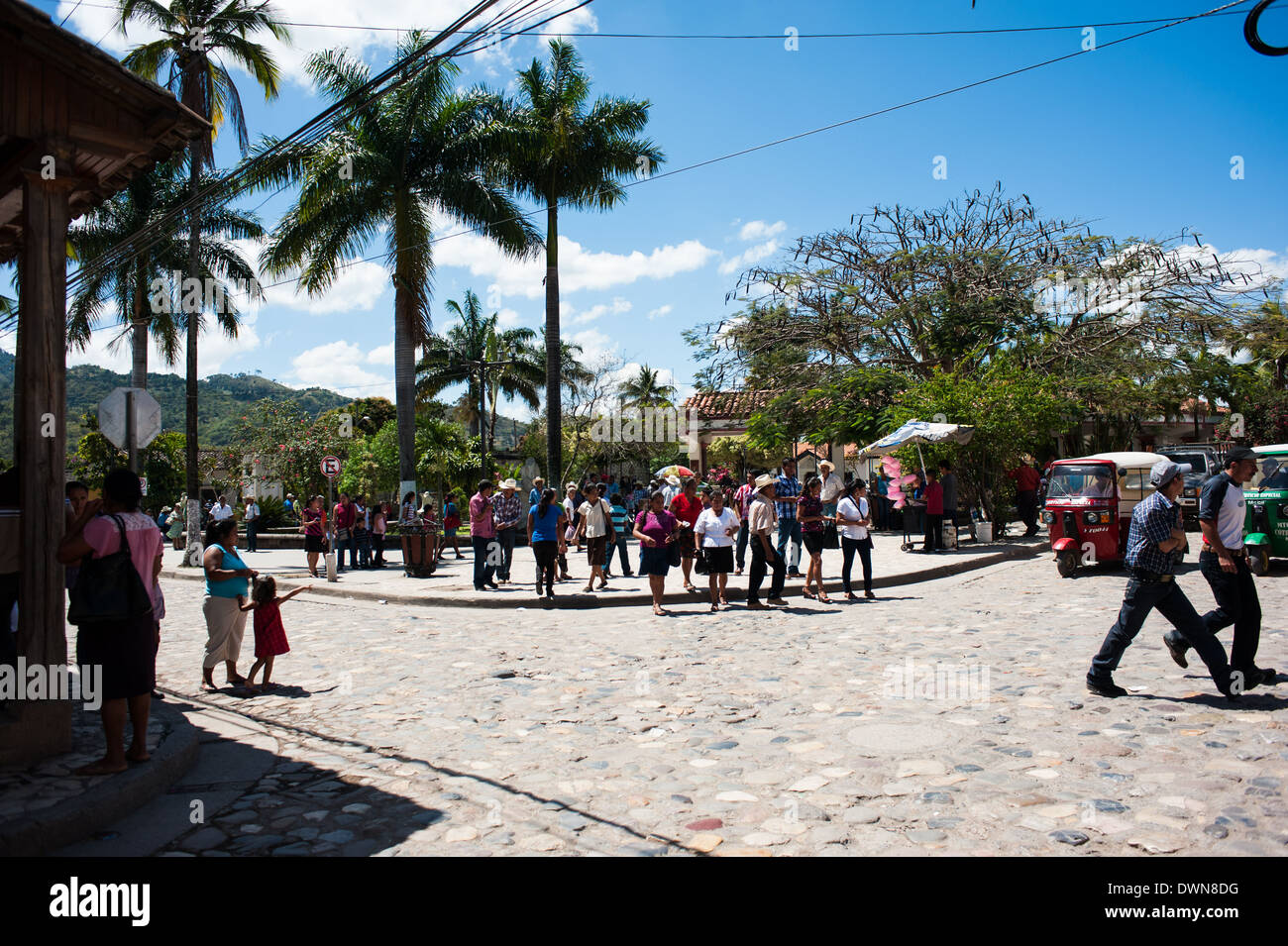 People walk through the busy Parque Central in the town of Copán Ruinas in Honduras. - Stock Image