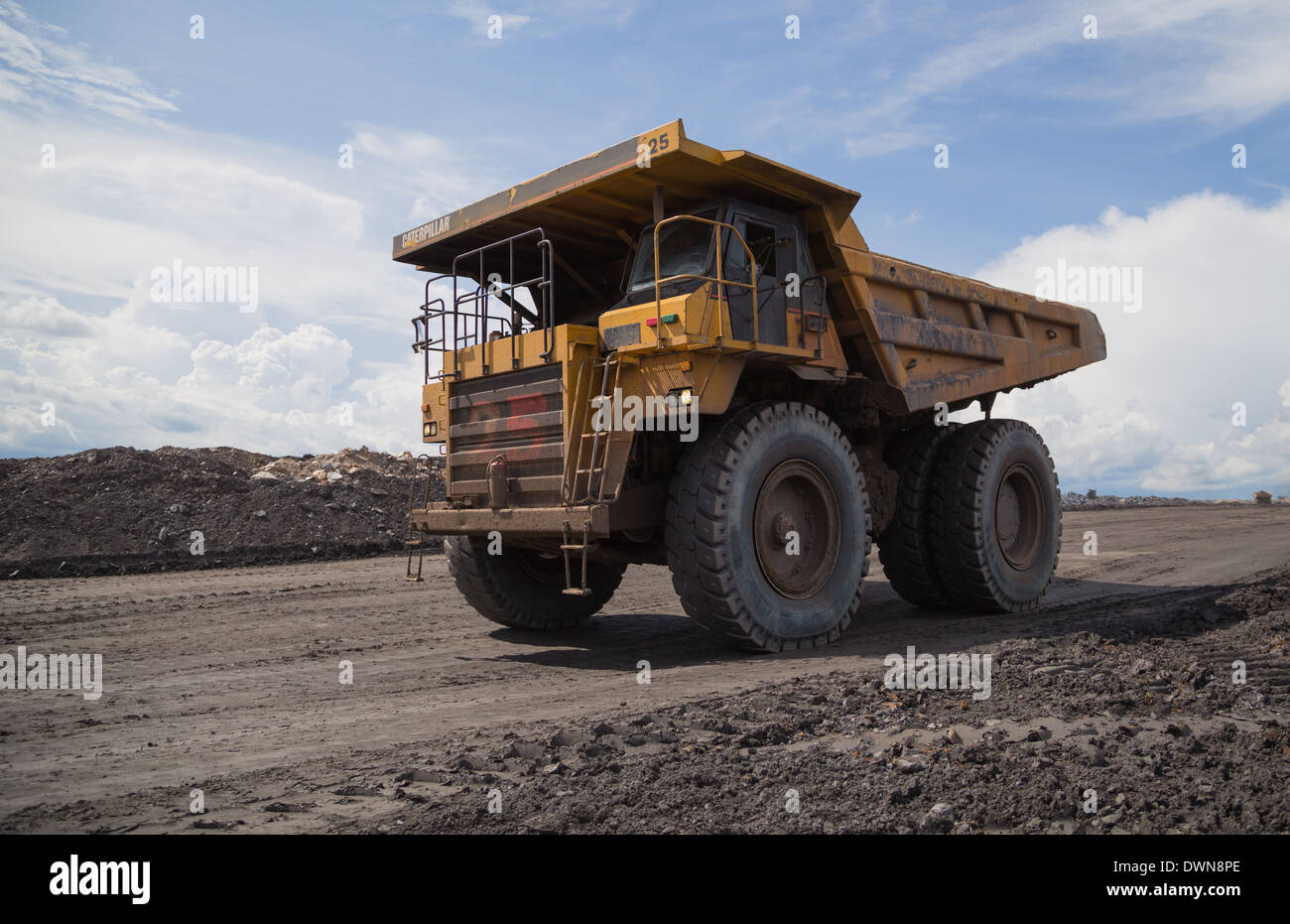 A caterpillar mining truck returns from dumping waste material on a stockpile in a large open cast copper mine. - Stock Image