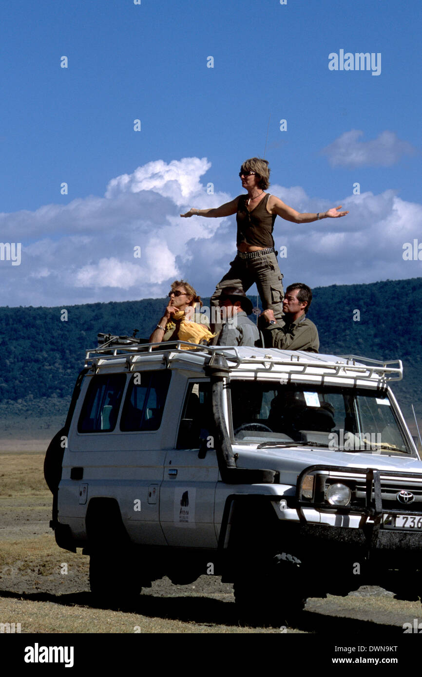 Tourists watching wildlife from a vehicle in Ngorongoro Crater, Tanzania - Stock Image