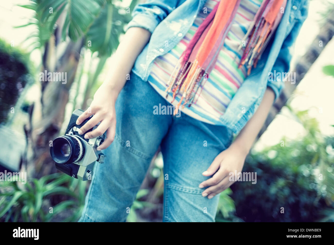 Woman wearing jeans and denim shirt holding camera outside - Stock Image