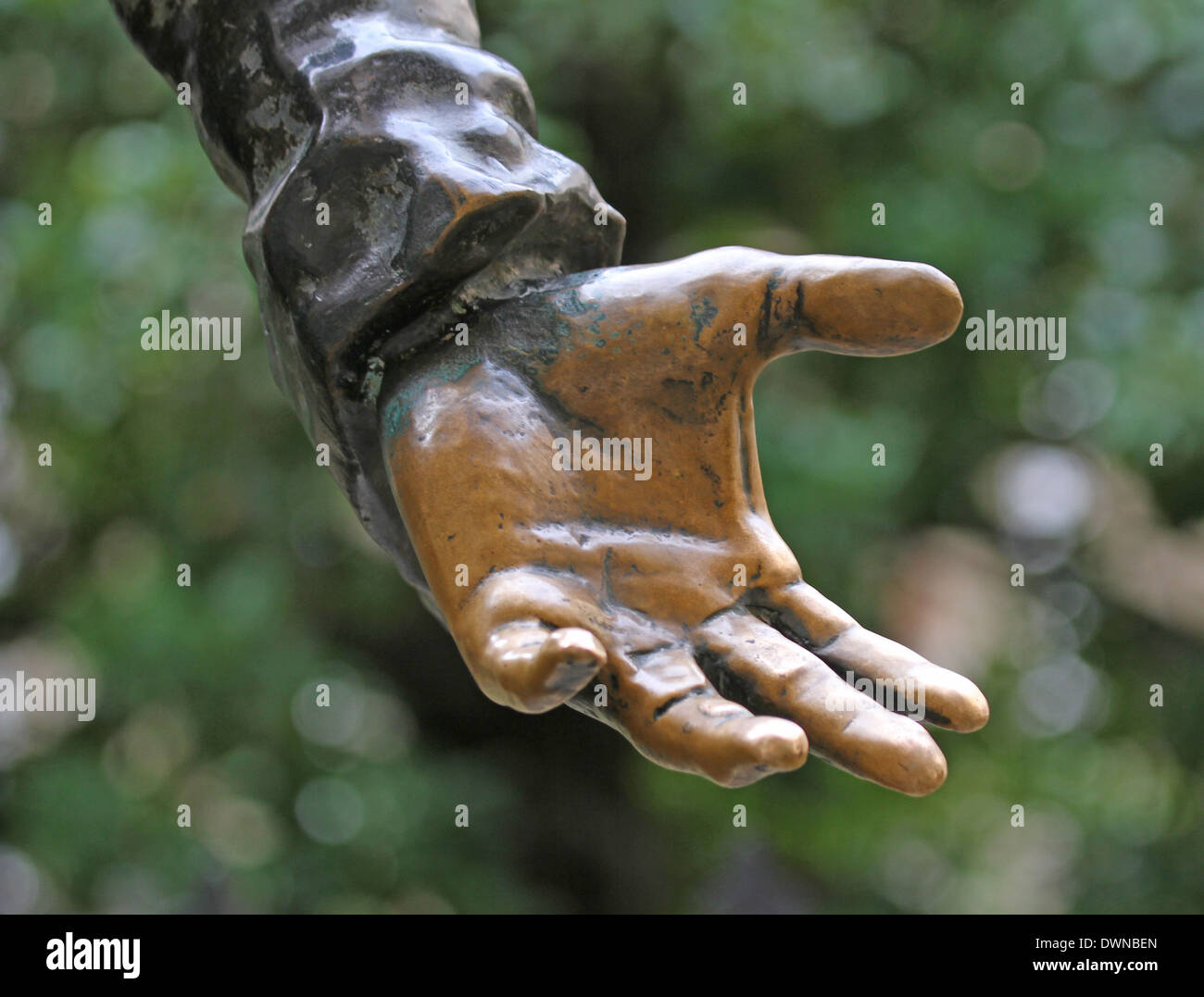 bronze hand stretches to offer something to people - Stock Image