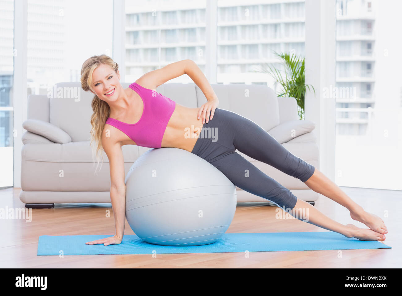 Cheerful fit blonde doing side plank with exercise ball - Stock Image