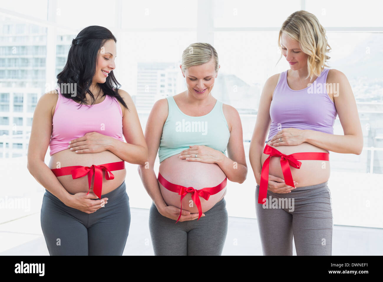 Cheerful pregnant women standing with red bow around bumps Stock Photo