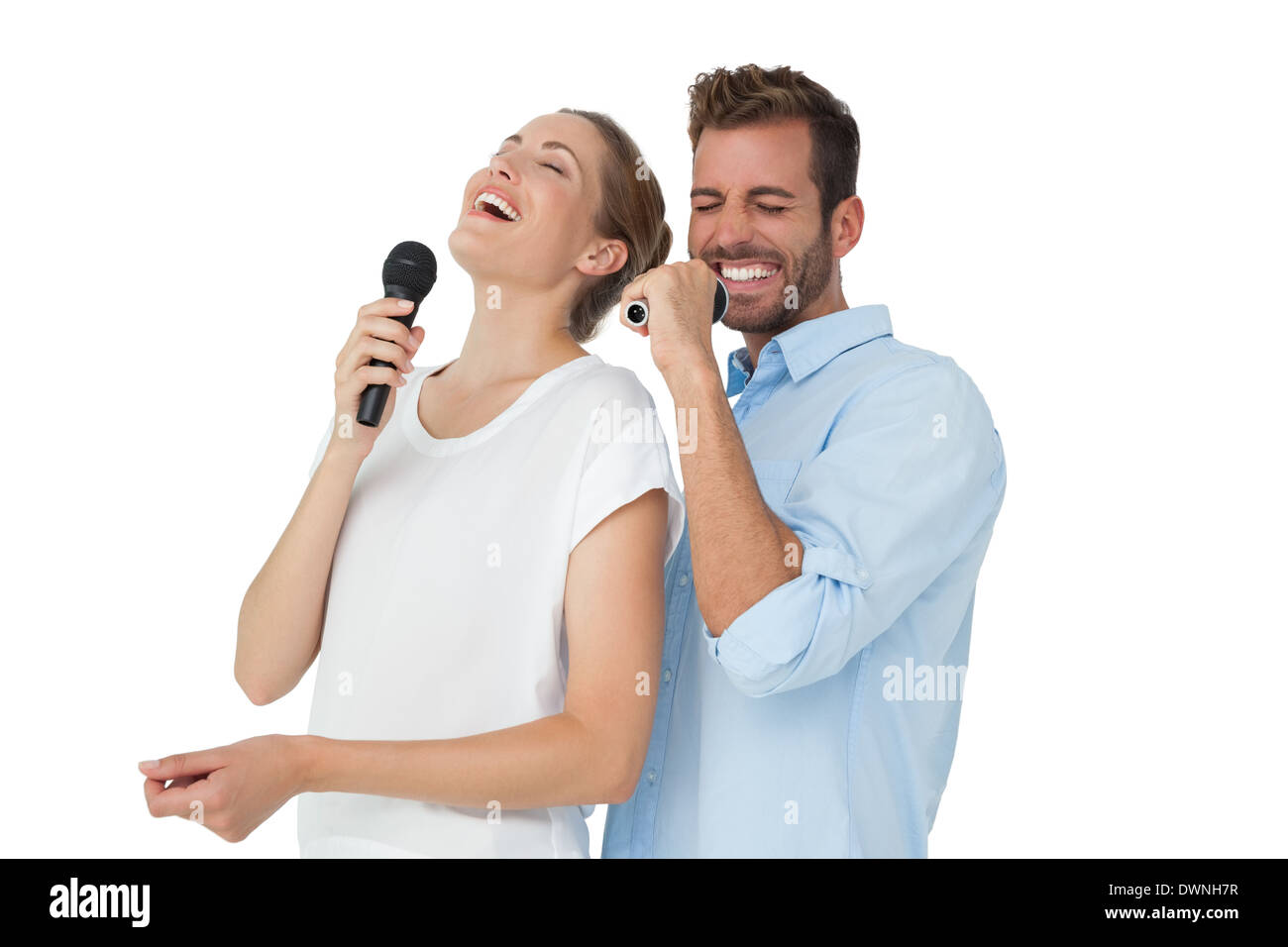 Cheerful couple singing into microphones - Stock Image