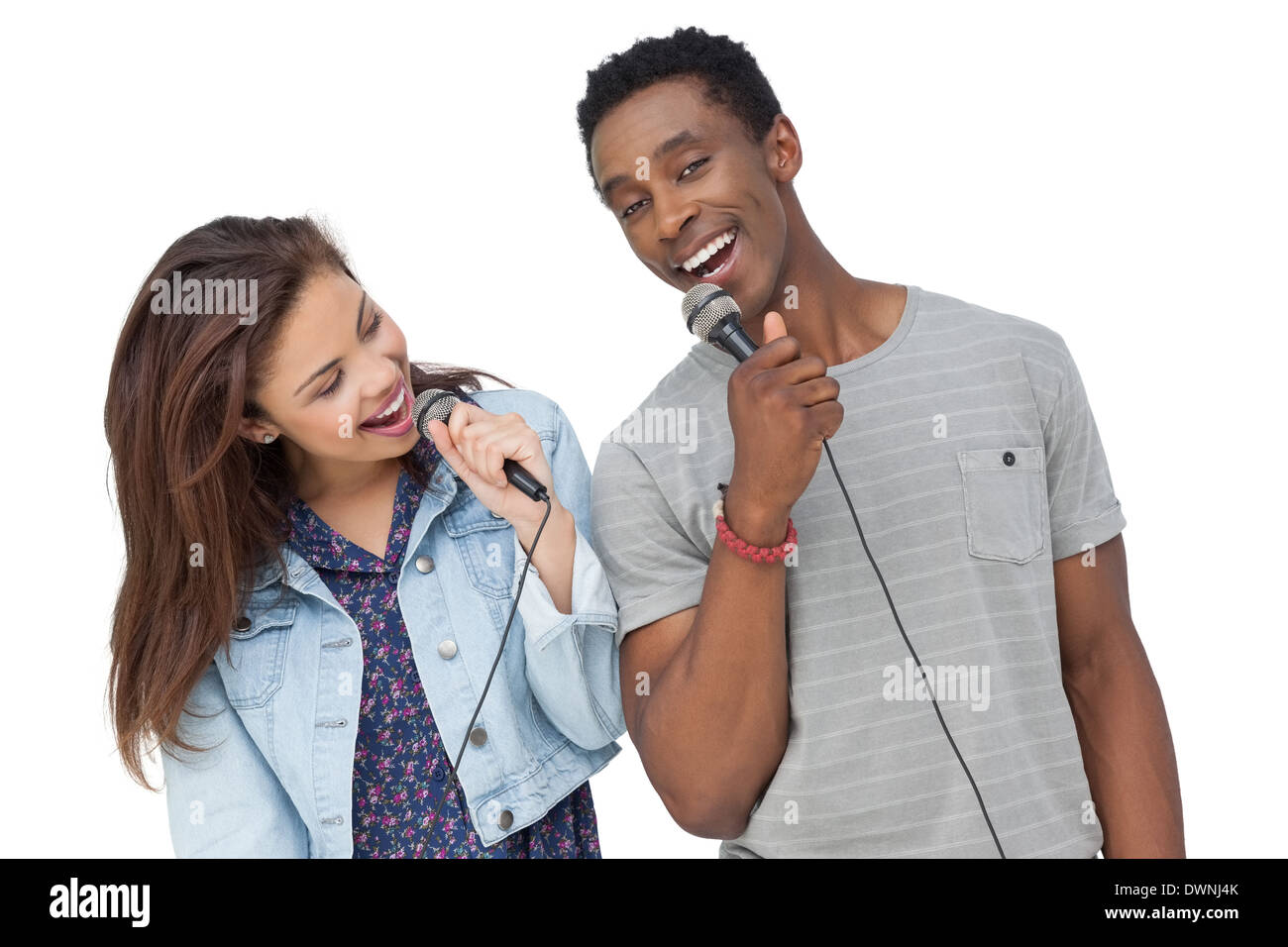 Young couple singing into microphones - Stock Image