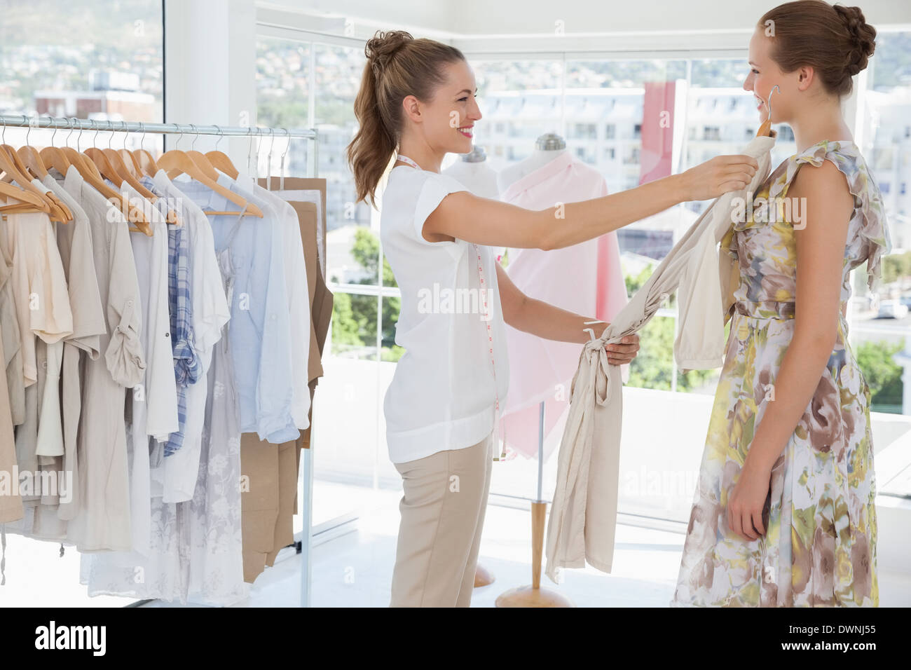 Saleswoman assisting woman with clothes at clothing store - Stock Image