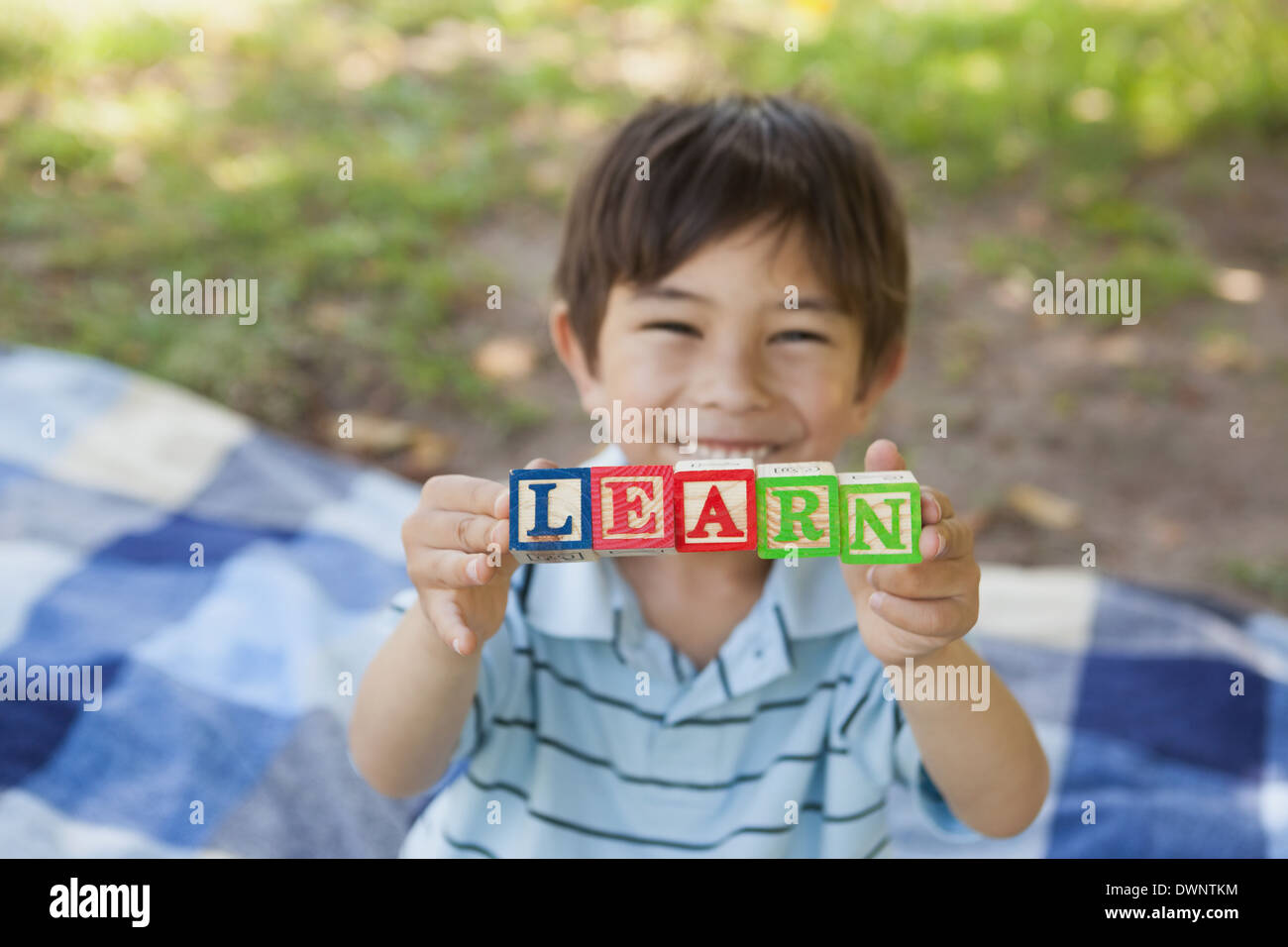 Happy boy holding block alphabets as 'learn' at park - Stock Image