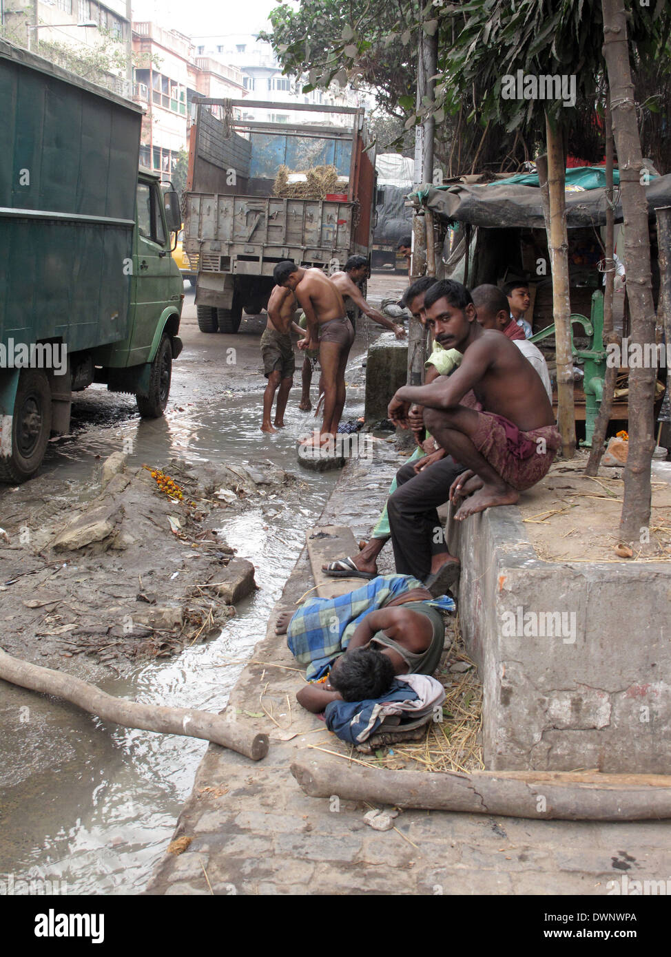 Streets of Kolkata. Indian people wash themselves on a street , January 25, 2009. Stock Photo