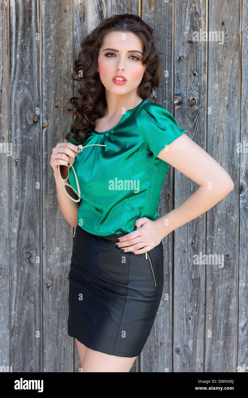 14b0681f05 Young woman wearing a black mini skirt and a green top - Stock Image