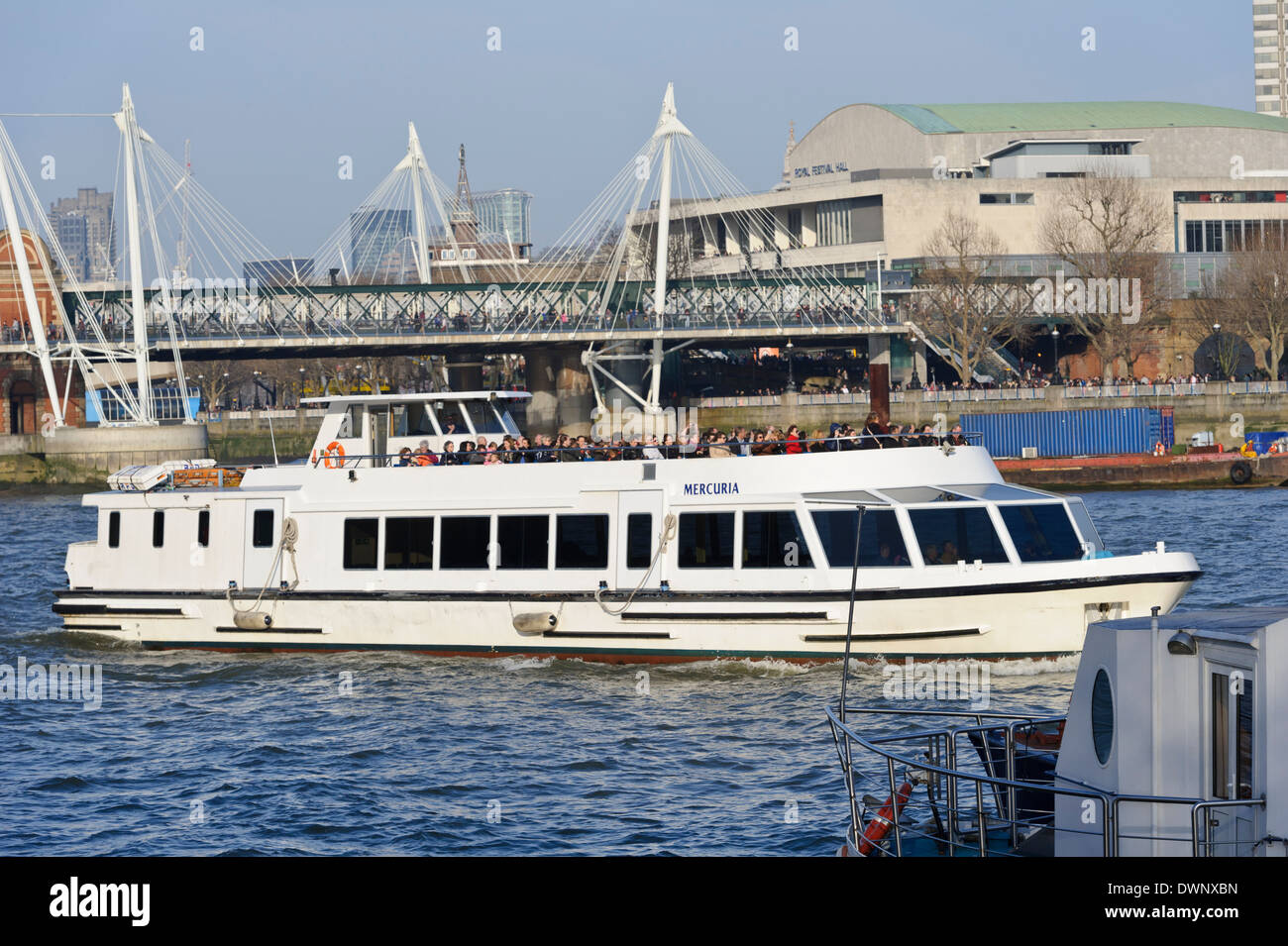 Tourists cruising on the Thames river with Hungerford bridge in background, London, England, United Kingdom. - Stock Image