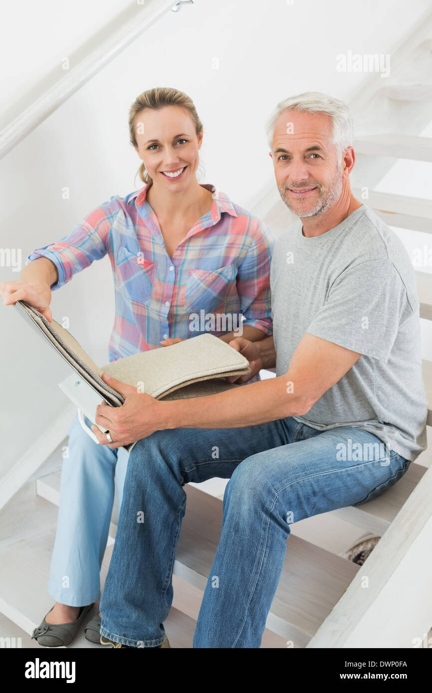 Happy couple picking out carpet samples together Stock Photo