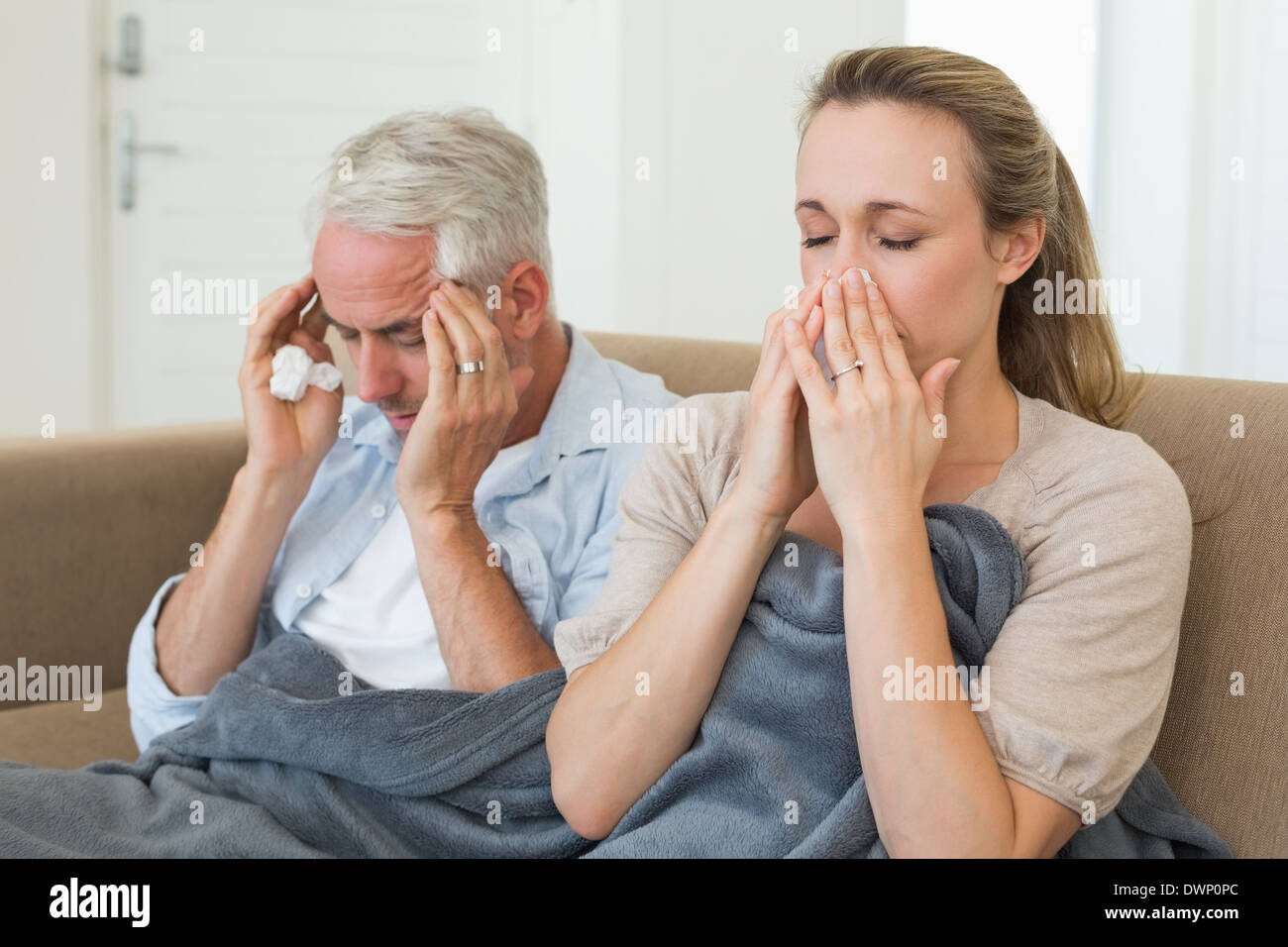 Sick couple sitting on the couch under a blanket - Stock Image