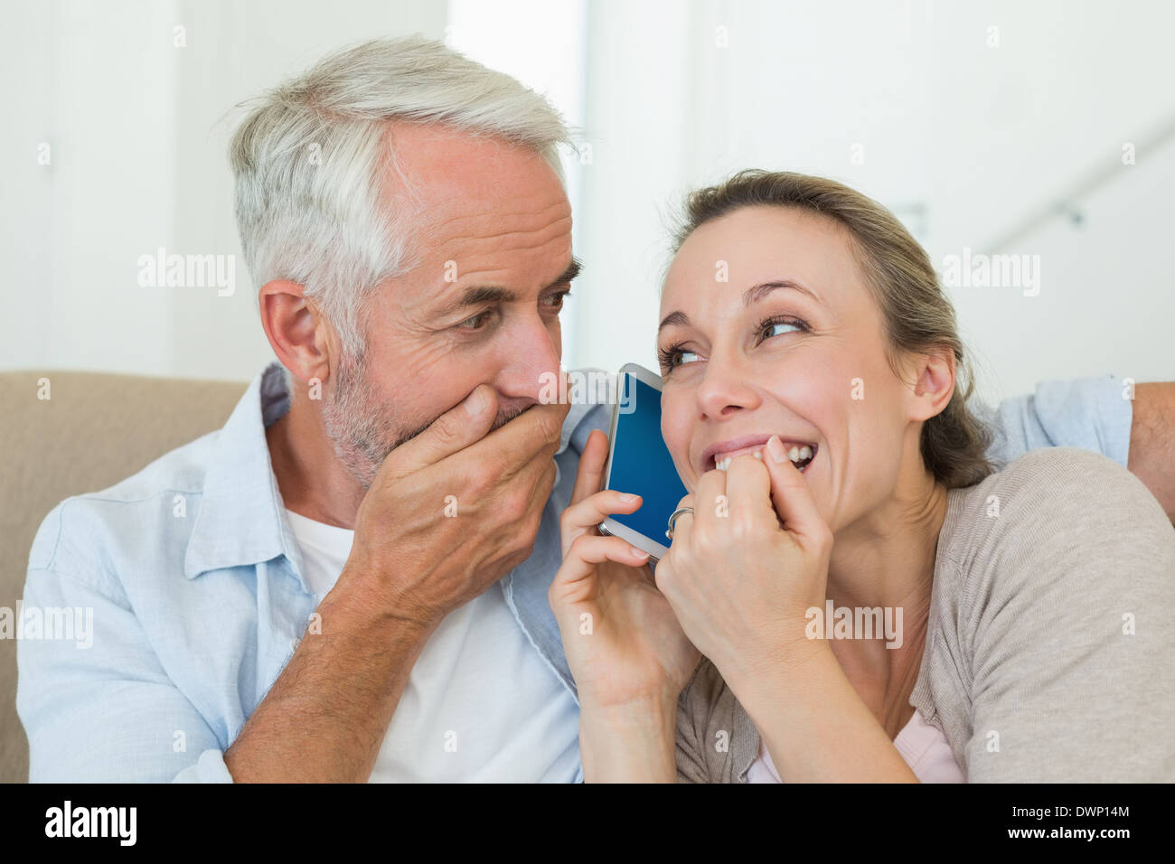 Happy couple listening to phone call together on the couch - Stock Image