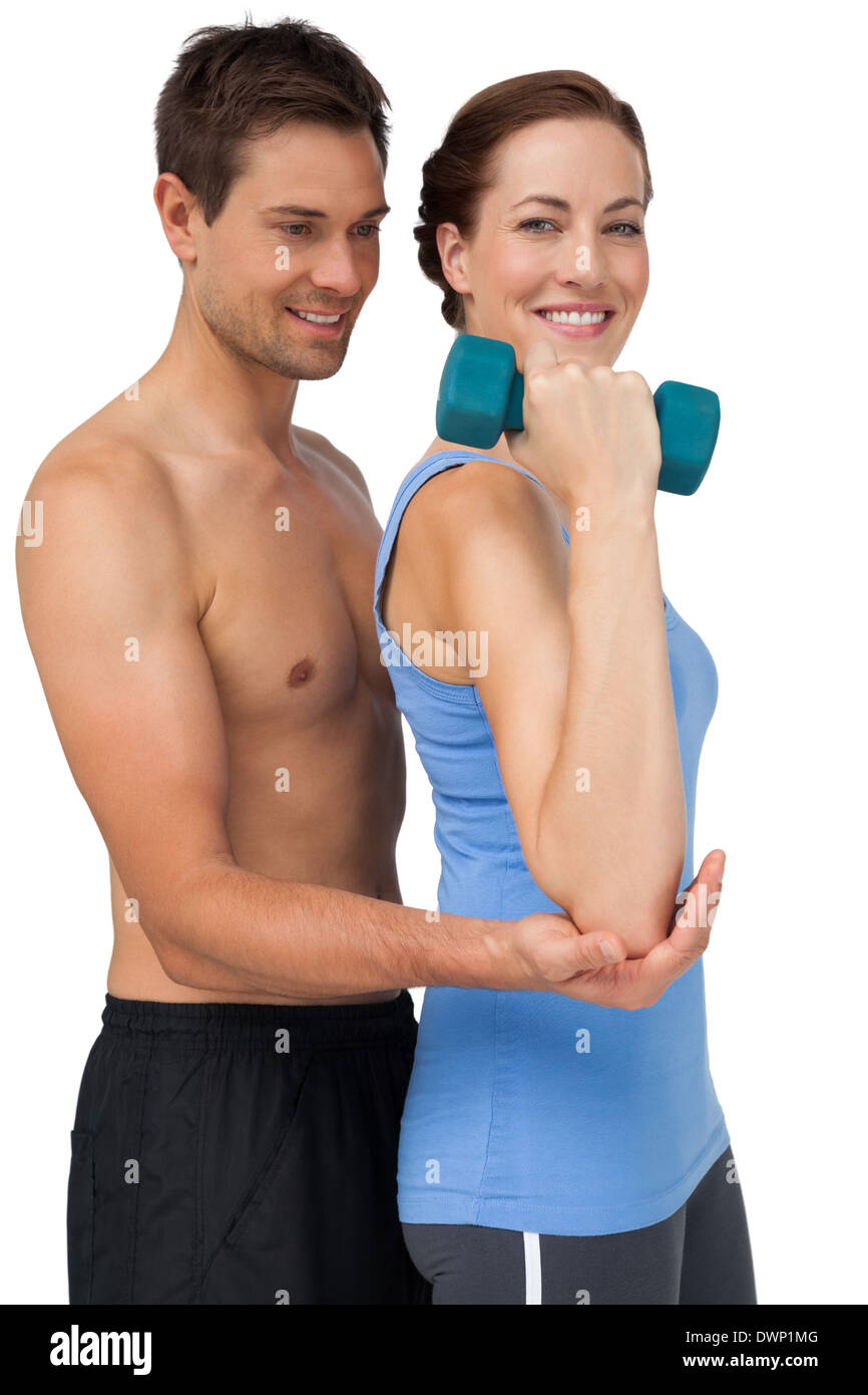 Male trainer assisting woman with dumbbell Stock Photo