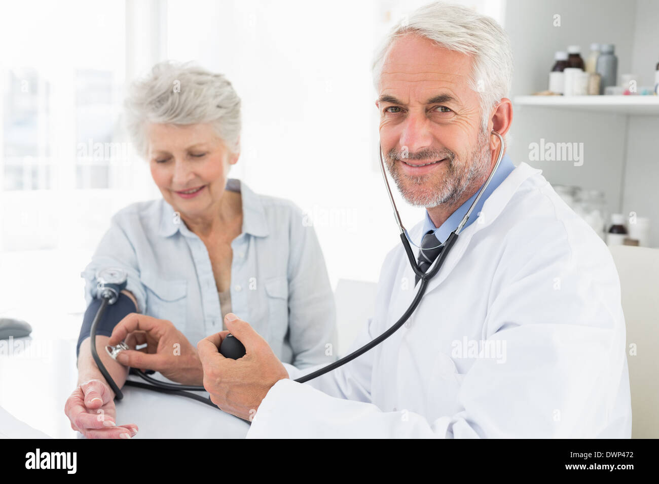 Doctor taking the blood pressure of his retired patient - Stock Image