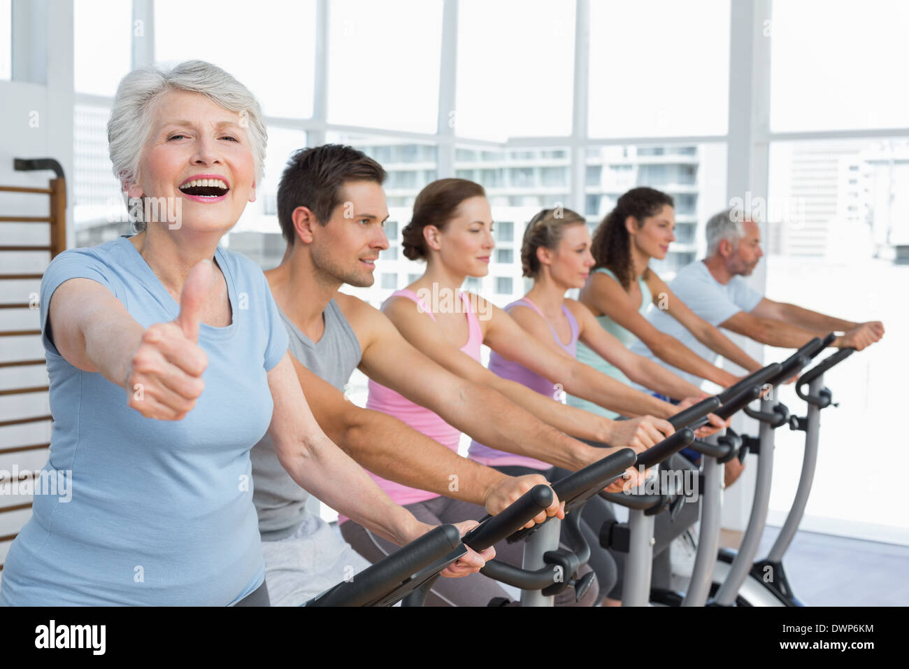 Woman gesturing thumbs up with class at spinning class - Stock Image