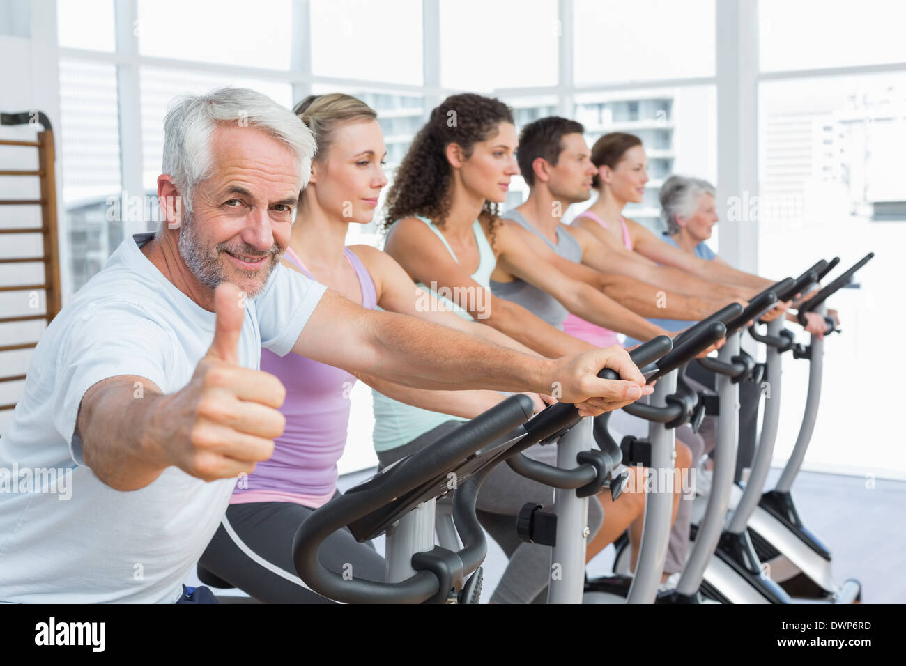 Man gesturing thumbs up with class at spinning class - Stock Image