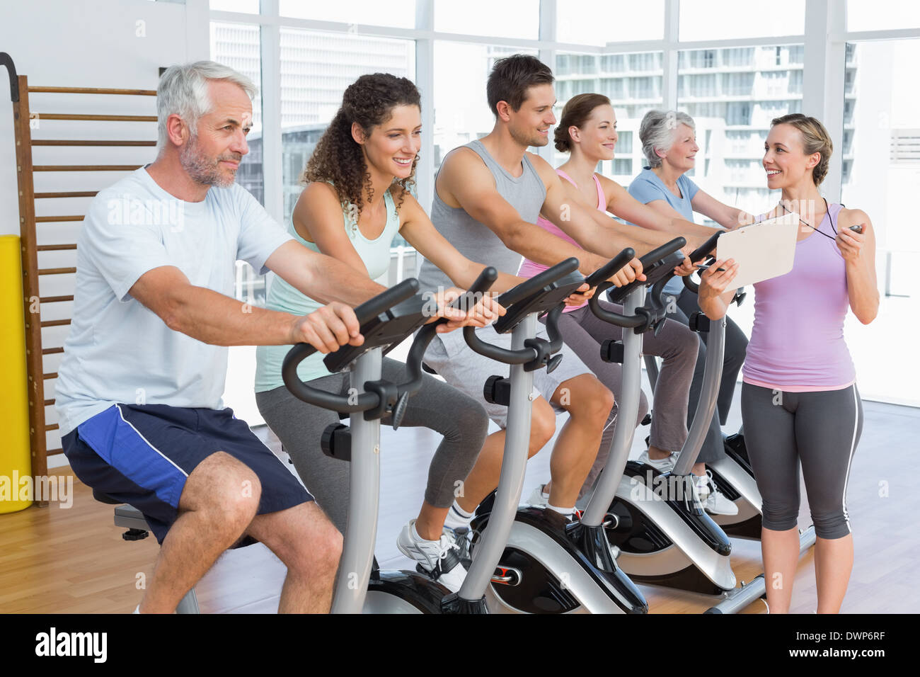 Trainer besides people working out at spinning class - Stock Image