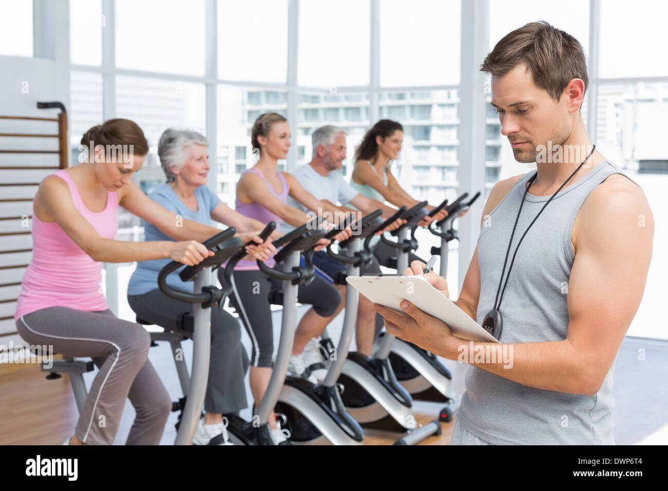 Trainer with people working out at spinning class Stock Photo