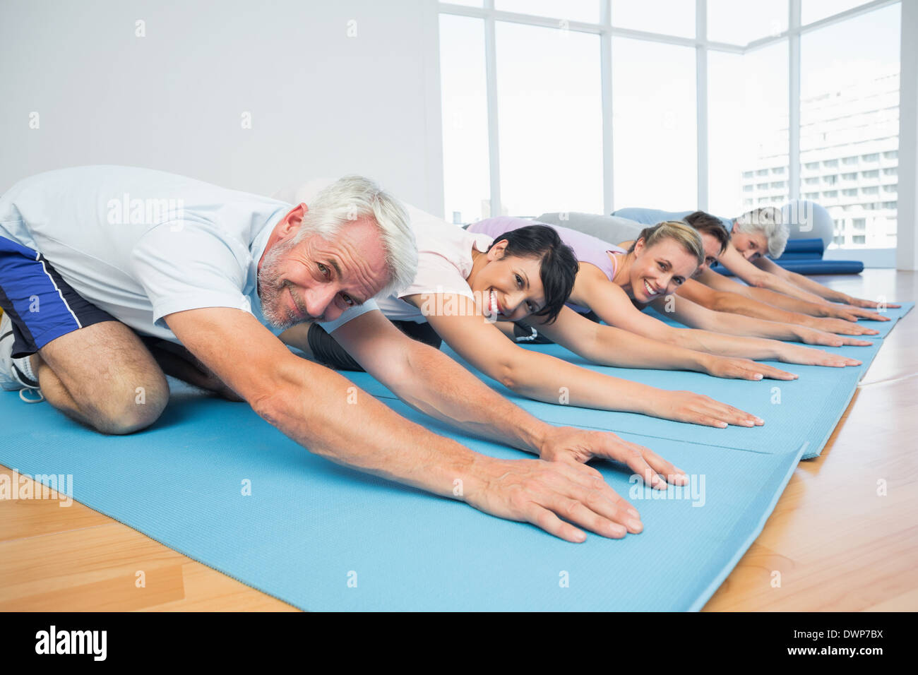 Portrait of fitness group bowing in row - Stock Image