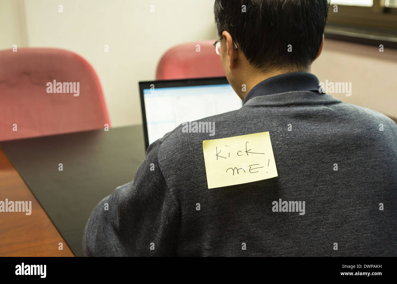 Office man with a yellow sticky note on his back, saying kick - Stock Image