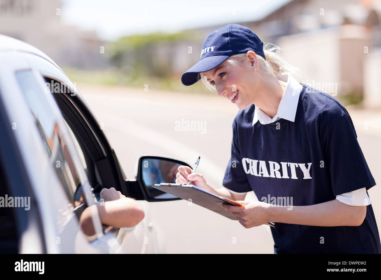 cheerful volunteer raising money for charity on street - Stock Image