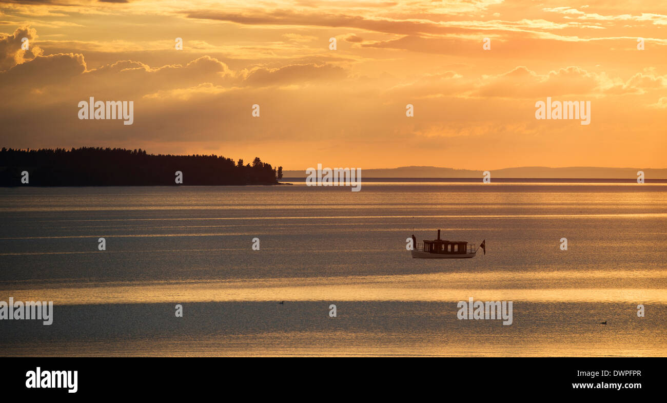 Tranquil summer night scene in Sweden. Silhouette of small steamboat on lake Vattern at sunset. Stock Photo