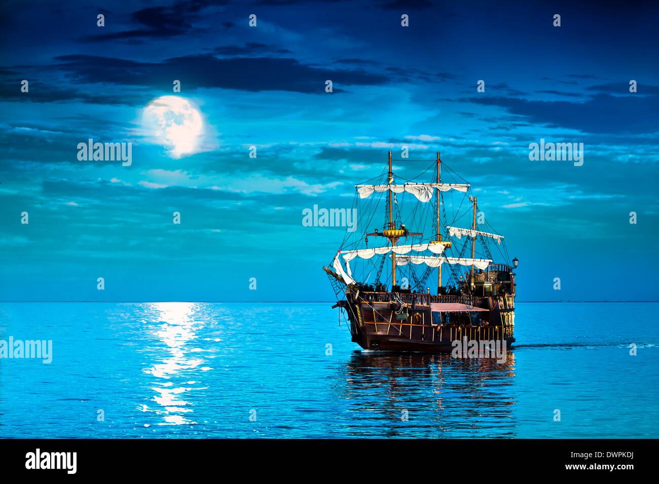 Old pirate ship sailing at Moon Stock Photo