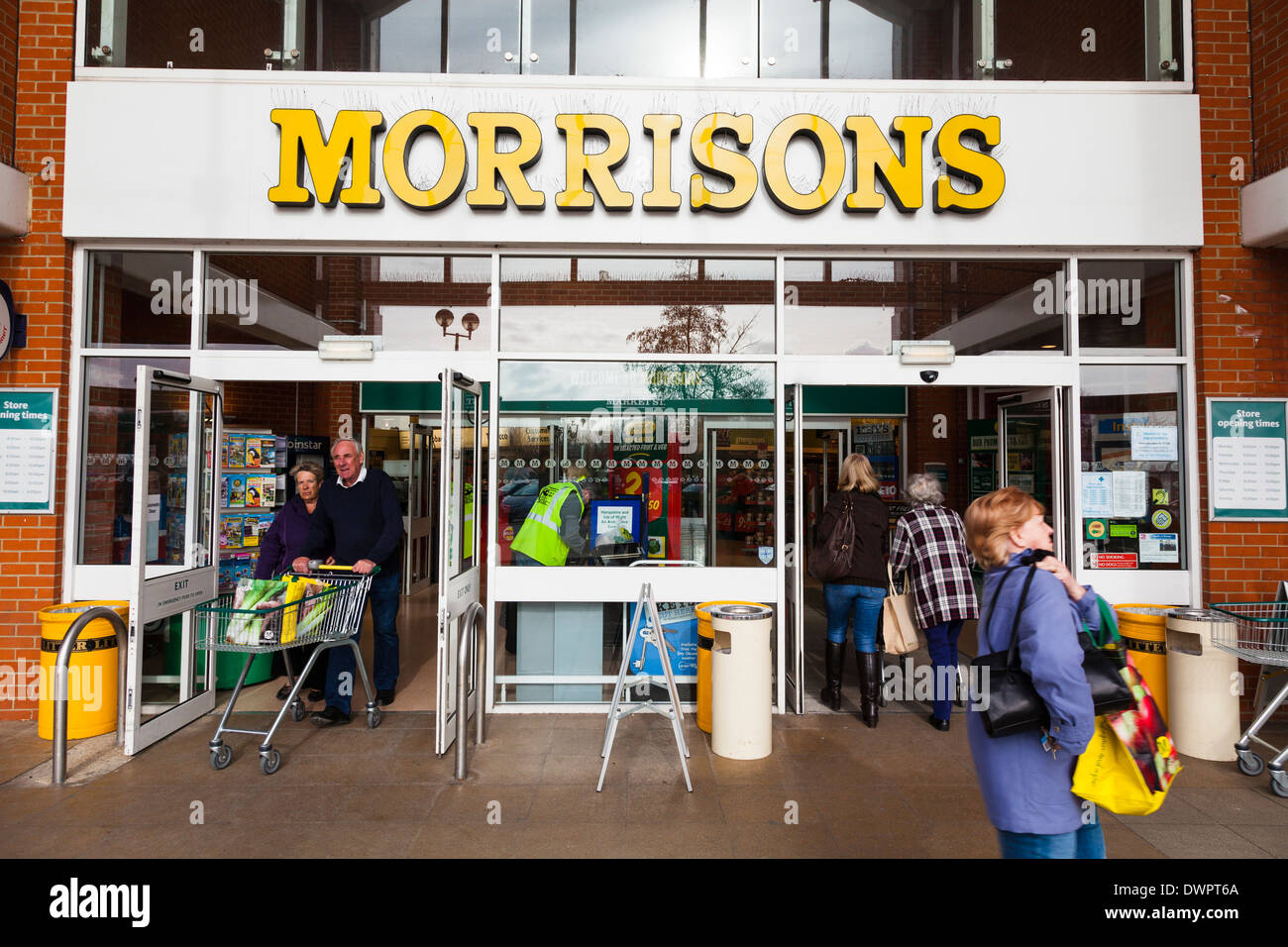 Customers entering and leaving a Morrisons Supermarket. - Stock Image