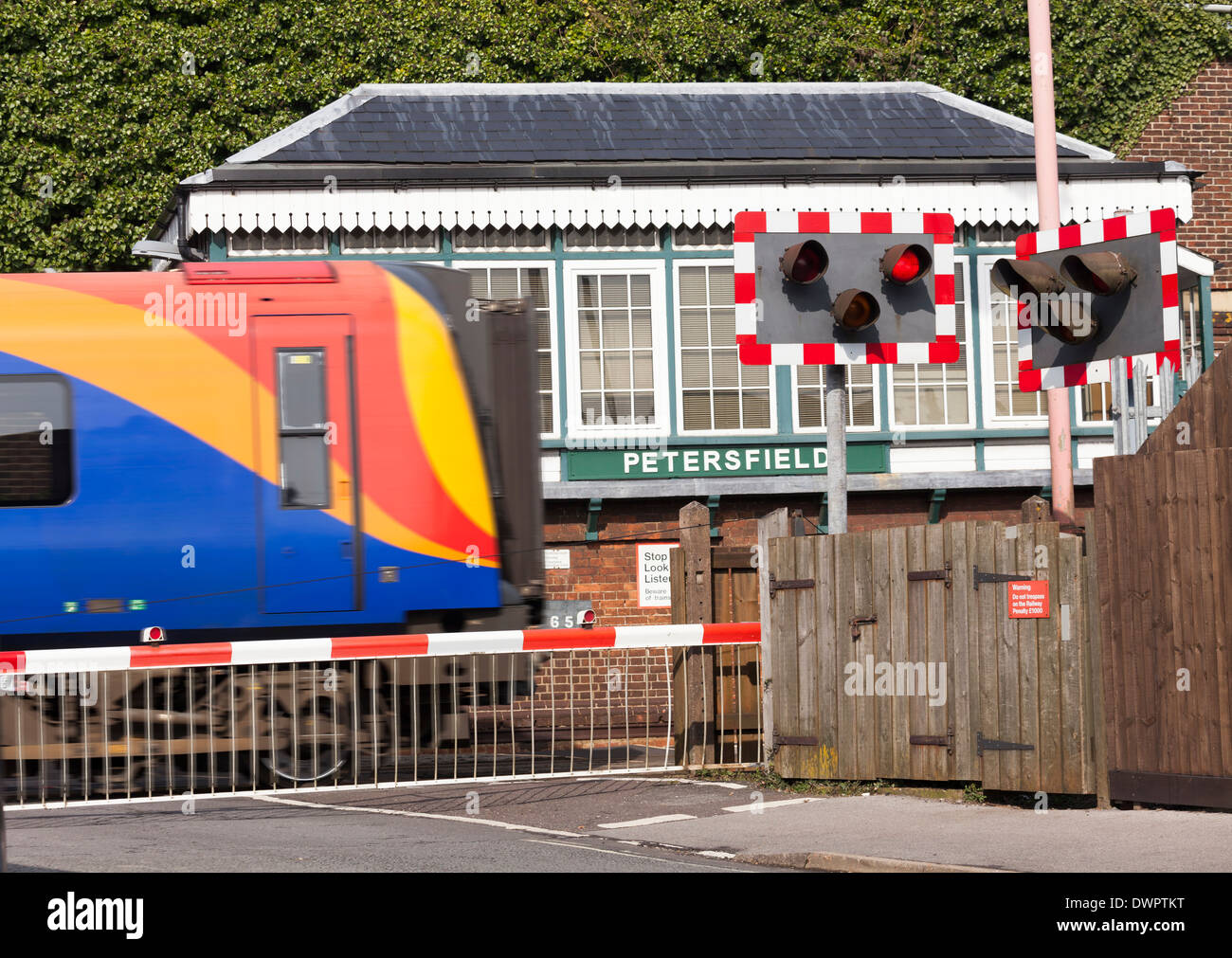 Train passing Petersfield 1880's Type 3 Signal Box with down full barrier type level crossing. - Stock Image