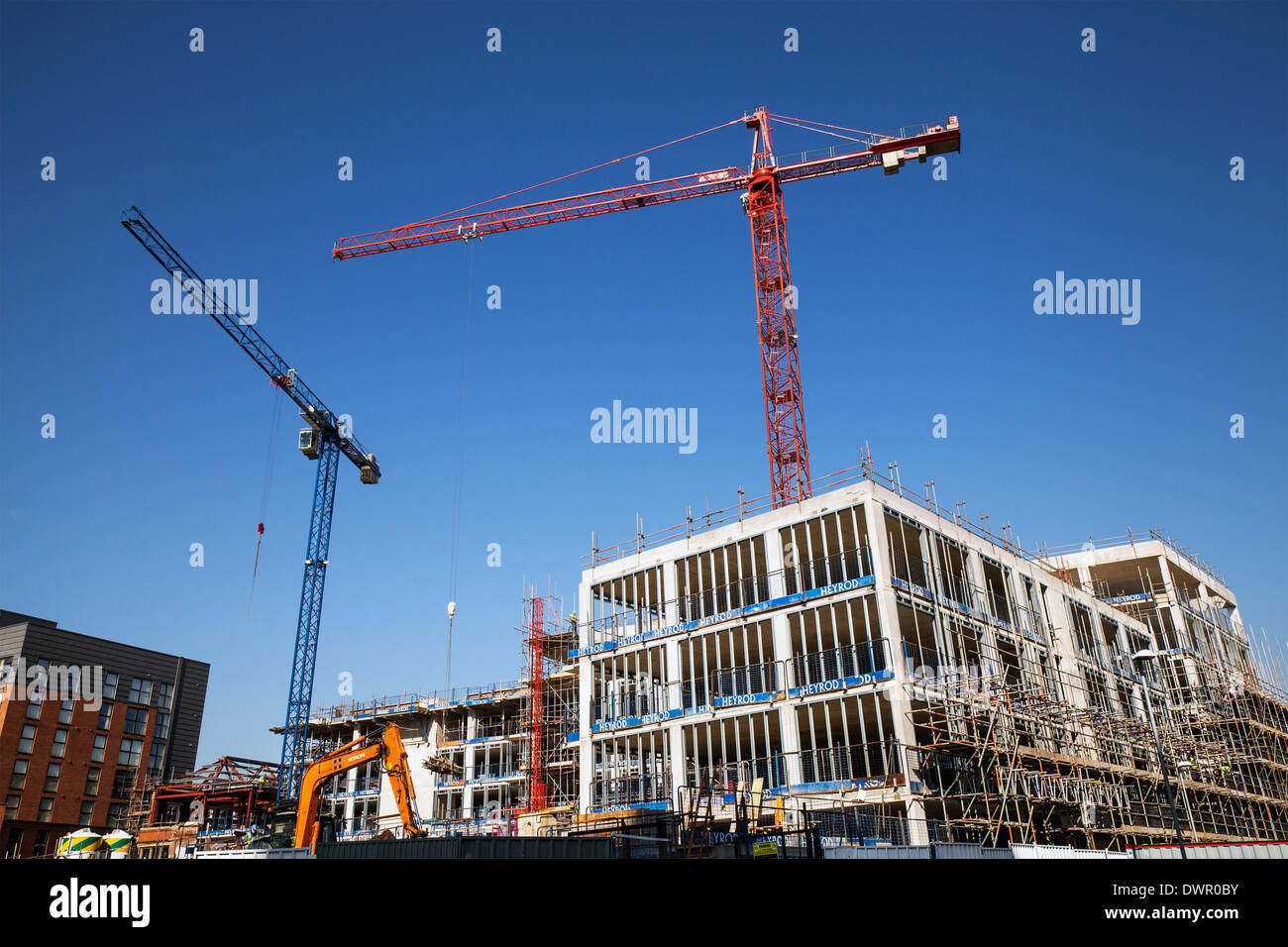 Manchester, UK 12th March, 2014.   City new build construction boom. HTC Cranes being used in building assembly - Stock Image