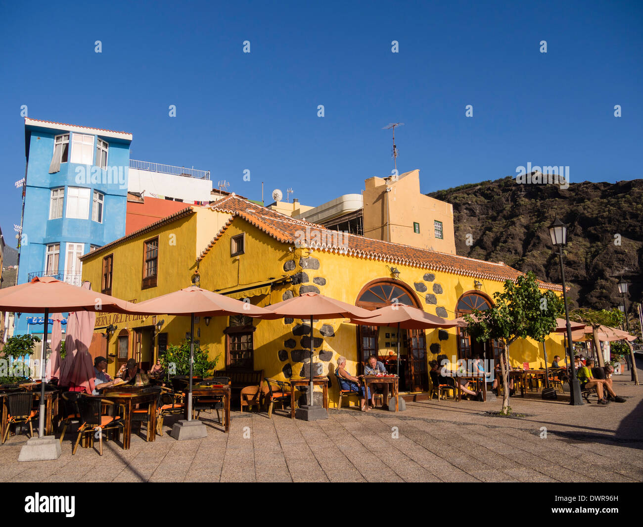 Tourists sit at the restaurant 'Taberna del Puerto' at the beach front of Puerto de Tazacorte on the Canary Island of La Palma. - Stock Image