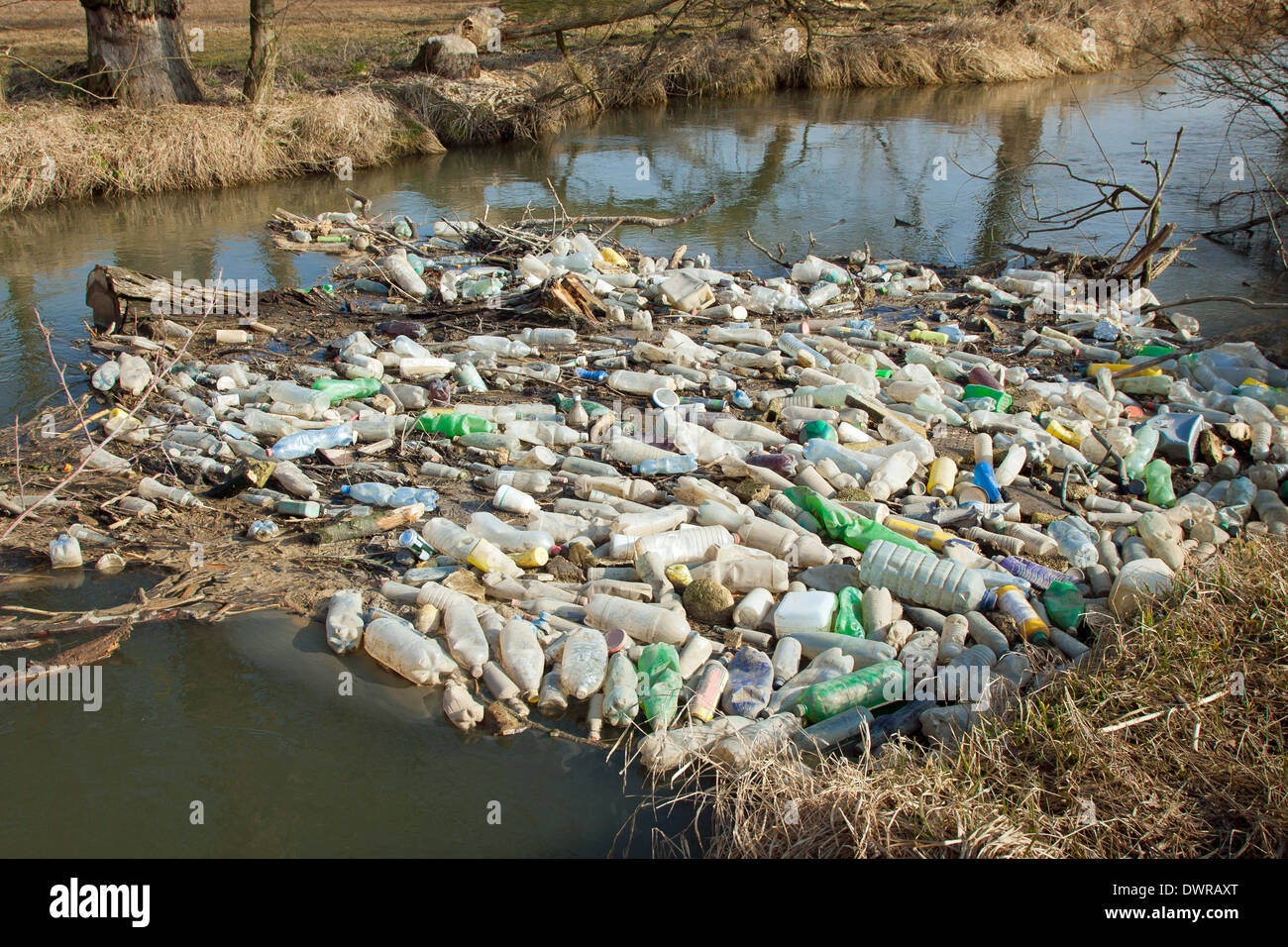 Environmental pollution. Plastic, glass and metal waste in river on early spring - Stock Image