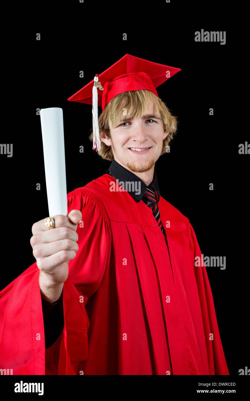 Handsome high school graduate wearing a red cap and gown isolated on black holding a diploma - Stock Image